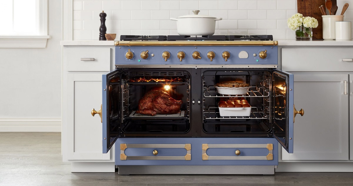 La Cornue Luxury Stainless Blue and Gold French Kitchen Range Cooking in the Oven with white cabinets